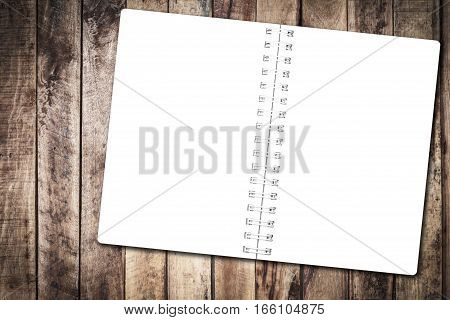Open notebook paper on wood background for design with copy space for text or image.