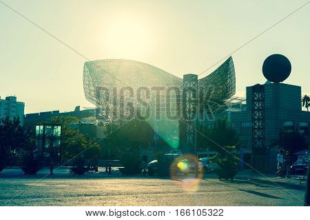 Barcelona, Spain - September 17, 2016; Stunning Frank Gehry fish sculpture shot into sun with lens flare and split tone filter effect on Barcelona waterfront Olympic Village