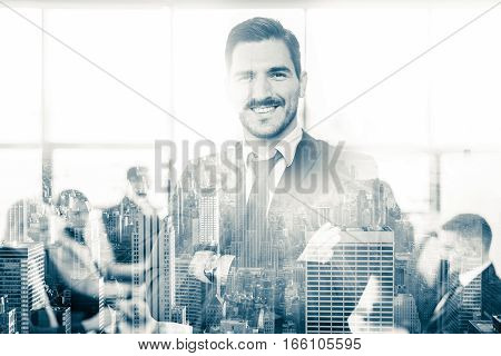 Black and white portrait of successful team leader and business owner proudly standing with crossed arms with coworkers working in office in background. Business and entrepreneurship concept.