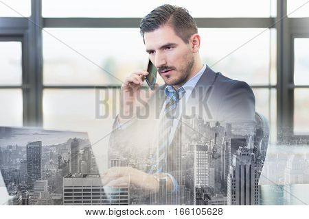 Portrait of successful corporate businessman in bright modern office focused on data on his laptop computer while talking on mobile phone. Business and entrepreneurship concept.