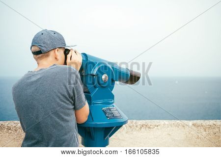 Teenager is looking through tourist telescope (works with 1 euro coin), exploring the area. Young teen is enjoying the sea view. Traveler.