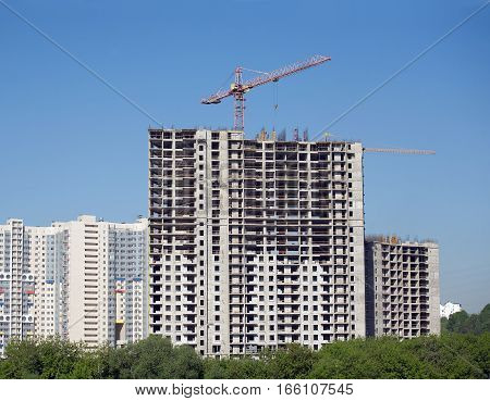 Hoisting tower crane in construction new apartment building process in residential district near river