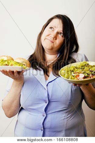 fat white woman having choice between hamburger and salad close up, unhealthy food concept
