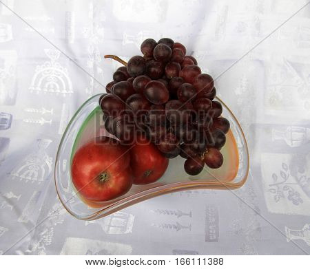 Fruits in glass vase on the fabric background