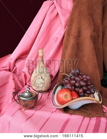 The still life with fruits and bottle