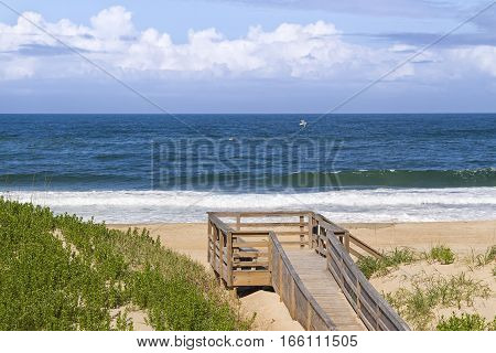 Waves break on a sandy North Carolina beach with a wooden boardwalk and deck on the dunes.