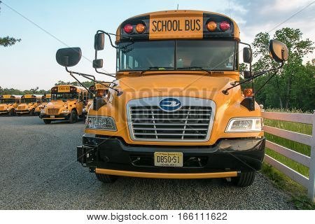 Somerset County, New Jersey, May 29, 2016: School buses are parked in a school bus parking lot by a field on a Sunday