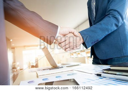 Businessmen shaking hands during a meeting in office.