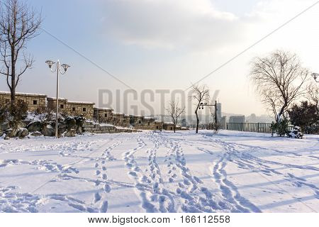 naksan park stone wall covered in snow with the view of the city in the back. Taken in Seoul South Korea