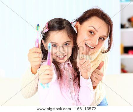 mom teaches daughter brushing teeth in bathroom
