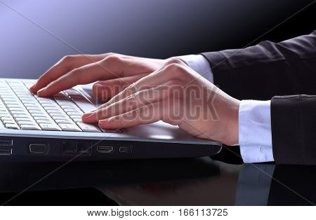 Closeup of male hands typing text on laptop keyboard