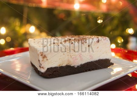 Candy Cane Ice Cream cake on a chocolate brownie in front of the Christmas tree