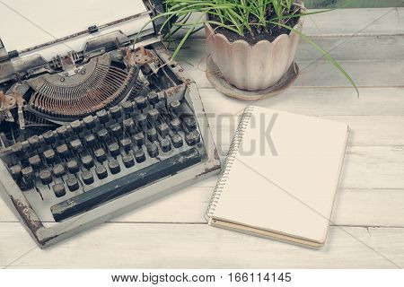 Dirty vintage tapewrite with plant and blank notebook on the wooden table