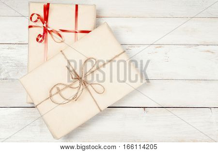 Two wrapped gift boxes on white wooden table with copy space