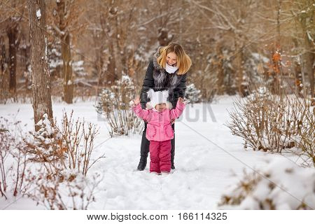 Mother and daughter walking on snow outdoors. Family walk in a winter park. Family happiness.
