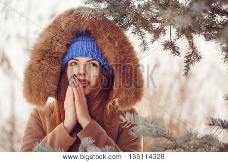 Cute teen girl in blue knitted hat and scarf fur hooded jacket winter walks in the park. She warms the breath of a person hands. Outdoor Activities. Youth fashion. Close-up portrait