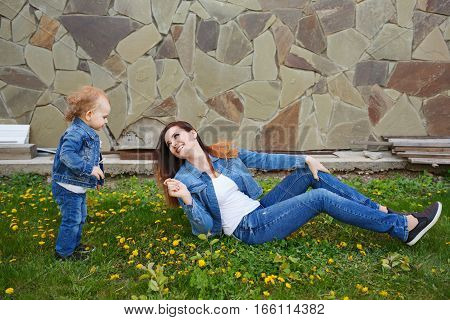 Mother and daughter in a spring park. Mother sits on a green lawn and the daughter goes to her. Girls dressed in denim jackets and jeans. Spring mood. Family time.