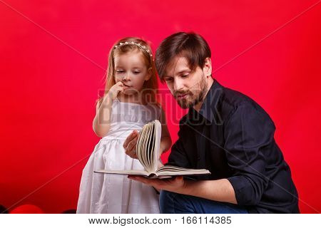 Father and daughter read a book. Girl emotionally reacts to an interesting story. They choose a fairy tale. Tales on roles. The concept of home education.