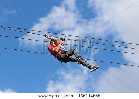 July 15, 2016 Banos, Ecuador: a man hags on zip-line cable slide in Banos Ecuador with mobile phone in hand taking photos