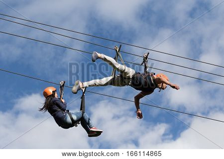 July 15, 2016 Banos, Ecuador: a man and a woman slides in tandem on zip-line across a canyon