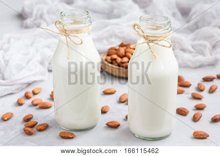Almond milk in glass bottles with almonds on background horizontal