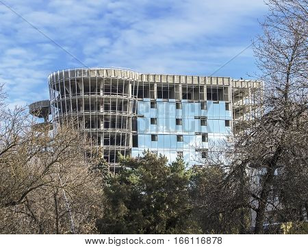 Unfinished building with clouds reflected in the glass against the blue sky