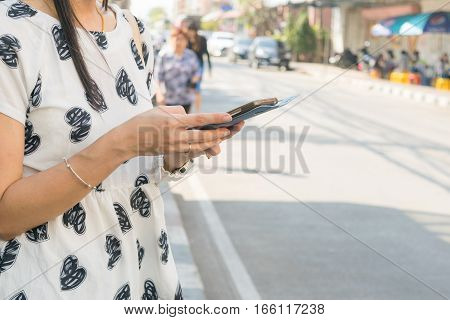 Women play mobile smartphone on a roadside.