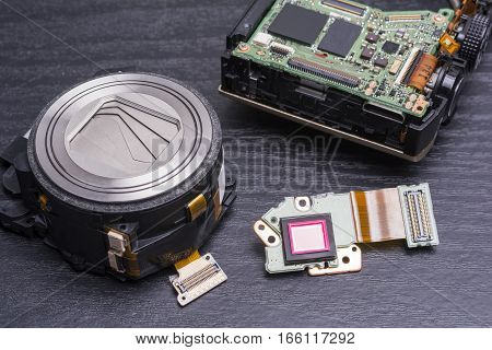 Decomposed of an digital compact camera parts on black table