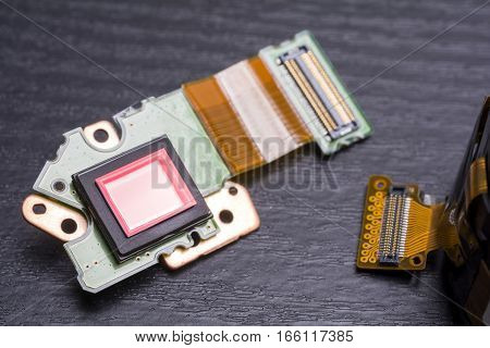 Sensor of decomposed digital compact camera on black table