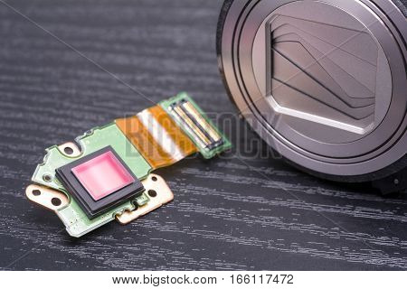 Sensor and lens housing of decomposed digital compact camera on black table