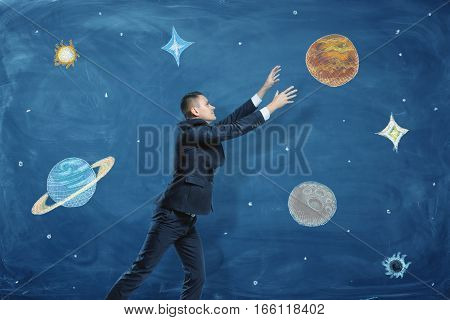 Businessman on blue chalkboard background trying to grasp a drawn planet among many others. Business and success. Dreams and aspirations. Road to one's goals.