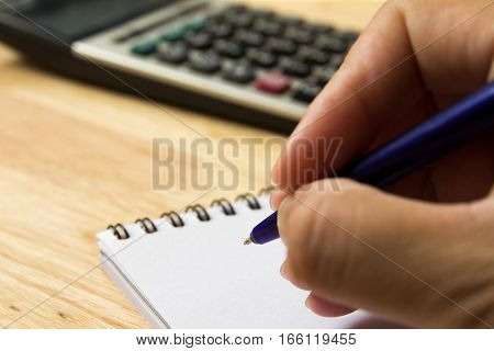 Man hold the pen for note on book with calculator (Concept for financial business and education)