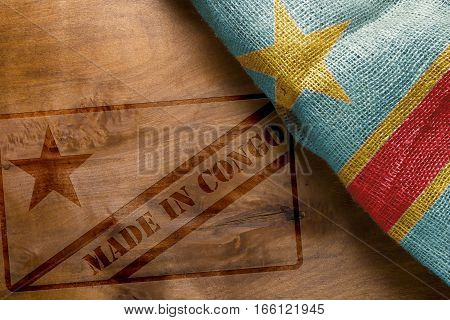 State of the Congo flag on a wooden background and stamp Made in Congo.