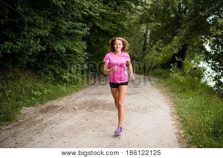 Road runner woman running in park. Feeling fit.
