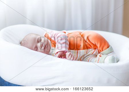 Cute adorable newborn baby sleeping peaceful in bed. New born child, little girl laying in bed. Family, new life, childhood, beginning concept.