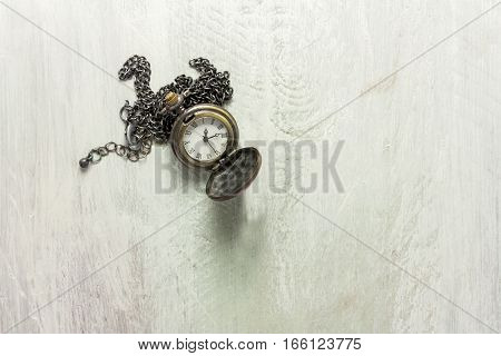 A photo of a vintage chain watch shot from above, with a place for text
