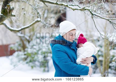 Happy mother holding newborn baby girl on arm after birth. family going from hospital to home. New born child sleeping. mum and child bonding. Outdoors, winter and snow.