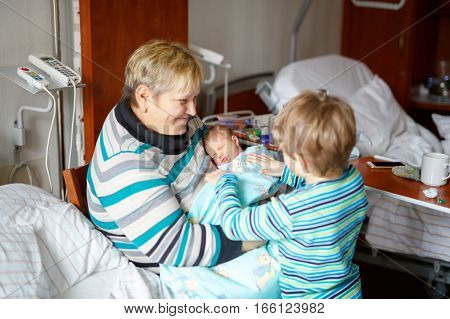 Happy grandmother holding newborn baby grandchild on arms in hospital. Proud brother kid boy with baby sister girl. Family, love, grandparents, siblings, carefree childhood.