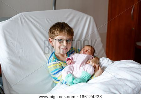 Happy laughing kid boy with glasses holding his sleeping newborn baby sister in hospital. Siblings, love. Children laying in bed in hospital. New born child sleeping. Kids bonding. Family love.