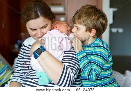 Happy little kid boy giving kiss his sleeping newborn baby sister in hospital. Mother holding baby girl on arm. Siblings, love. Family on bed in hospital. New born child sleeping. Kids bonding.