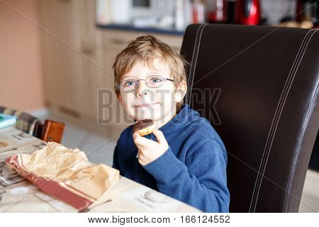 Adorable little school boy eating donut indoor. Blond child in domestic kitchen or in school canteen Cute kid and unhealthy sweet food