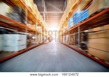 Large industrial warehouse. Long shelves with a variety of boxes and containers. Motion blur effect. Bright sunlight.