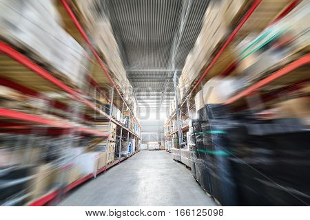 Warehouse industrial and logistics companies. Many boxes packed in a black stretch film. The boxes on high shelves stocked. The effect of motion blur.