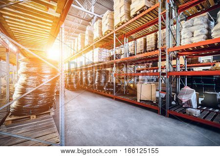 Warehouse industrial goods. Large long racks. Cardboard boxes and coiled plastic tube. Bright sunlight.