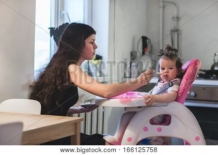 Young mother feeding daughter sitting in the highchair. Furnished home kitchen.