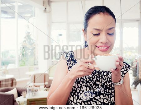 Happy woman holding cup of capuccino in burred coffee shop