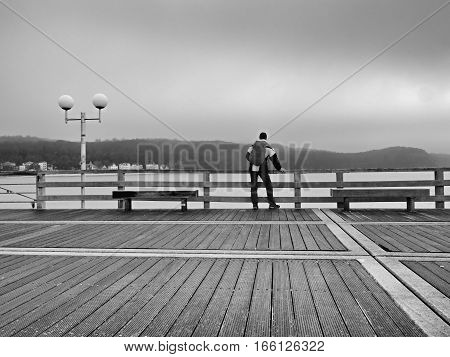 Tourist In Autumn Mist On Wooden Pier Above Sea. Depression, Dark  Atmosphere