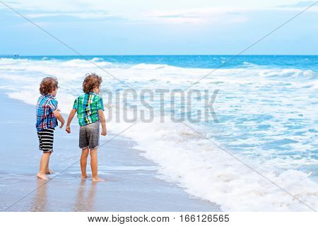 Two little kids boys on the beach of ocean looking on dusk, sunset and horizon. Funny cute children, happy siblings making vacations and enjoying summer in Miami, Florida