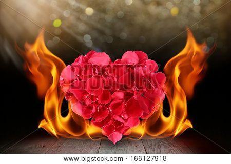 Rose petals heart shape with blaze fire flame on wooden deck