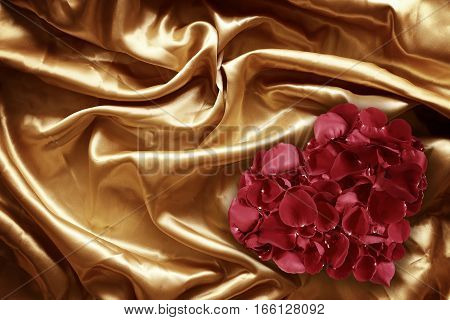 Rose petals on gold fabric silk for background